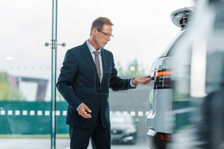 side view of businessman in eyeglasses choosing new car in dealership salon