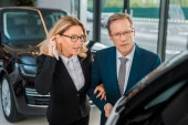 businessman and businesswoman with smartphone choosing new car in dealership salon