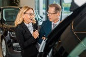 businessman and smiling businesswoman with smartphone choosing new car in dealership salon