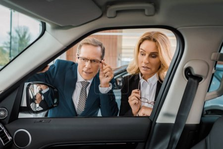 businessman and businesswoman checking new car in dealership salon