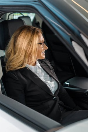 stylish businesswoman in suit and eyeglasses sitting in new car