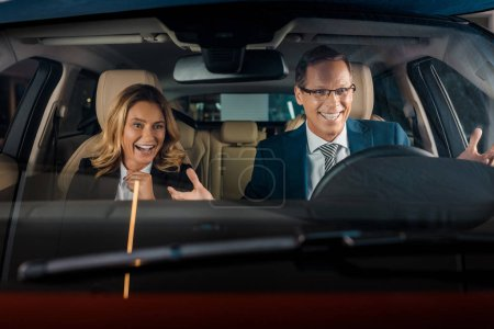 portrait of cheerful business couple in new car for test drive