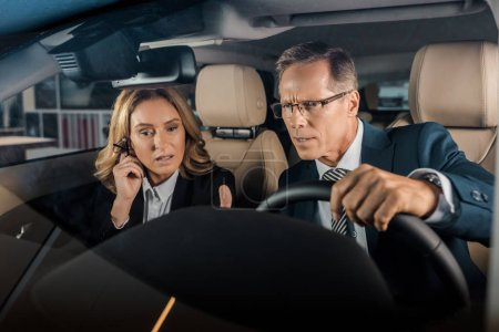 Photo for Portrait of pensive business couple in new car - Royalty Free Image