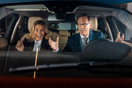 happy business couple sitting in new car