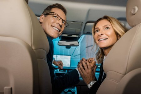back view of smiling couple in formal wear sitting in new car