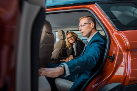 side view of businesspeople sitting on back sit in new car in dealership salon