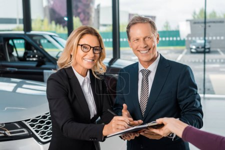 happy business couple signing papers for buying new car in showroom