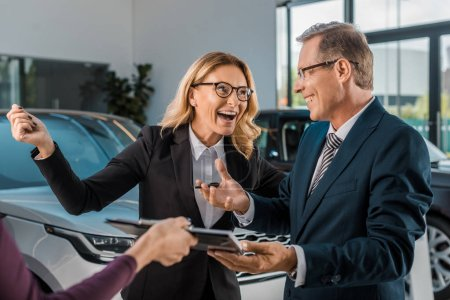 happy businesspeople and female car dealer with documents in showroom