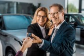 partial view of female car dealer giving car key to smiling couple in formal wear in dealership salon