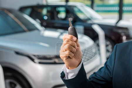 Photo for Cropped shot of businessman with car key in hand in dealership salon - Royalty Free Image
