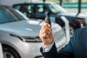 cropped shot of businessman with car key in hand in dealership salon