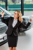 happy businesswoman in formal wear holding car key from new car in dealership salon