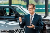portrait of smiling businessman with car key in hand in dealership salon