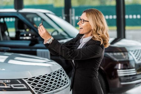 happy businesswoman in formal wear holding car key from new car in dealership salon