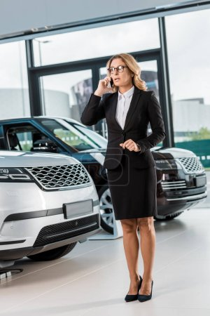 businesswoman in formal wear talking on smartphone in dealership salon