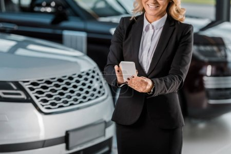 Photo for Cropped shot of female car dealer using smartphone at showroom - Royalty Free Image