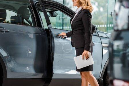 Photo pour Recadrée tir du garage automobile avec tablette voiture d'ouverture showroom - image libre de droit