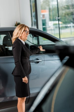 attractive female car dealer pointing at car in showroom