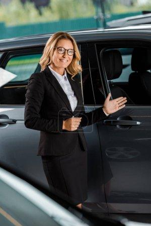 beautiful female car dealer pointing at car in showroom