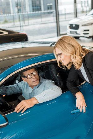 adult man sitting in sport car at showroom while smiling female car dealer standing outside