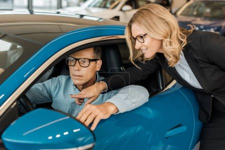 adult man sitting in sport car at showroom while female car dealer standing outside