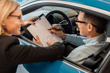 happy adult man signing contract with female car dealer while sitting in car