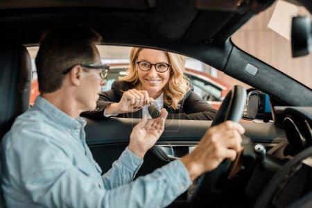 adult man taking car key from female car dealer at showroom while sitting inside car