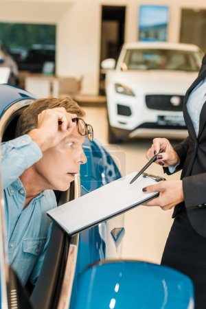 cropped shot of female car dealer showing car dealership contract to shocked adult man in salon