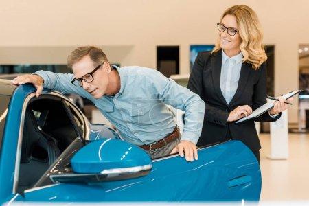 Photo pour Homme adulte contrôle de voiture de sport de luxe avec garage automobile au showroom - image libre de droit