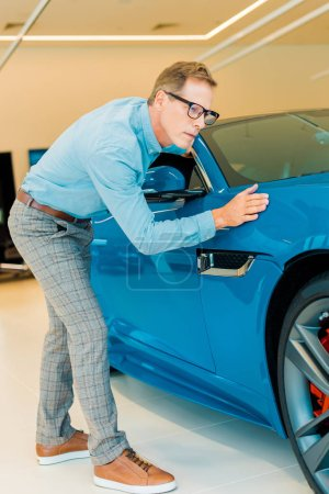 attractive adult man touching luxury sport car at showroom