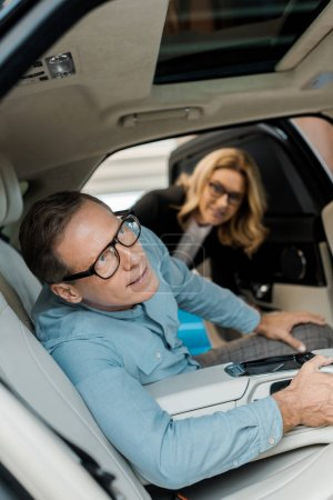 adult man checking luxury car interior at showroom while female car dealer looking at him
