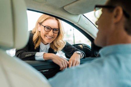 Photo pour Homme adulte parlant avec un concessionnaire de voiture féminin tout en étant assis à l'intérieur de la voiture au showroom - image libre de droit