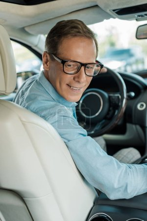 handsome adult man driving luxury car and looking back