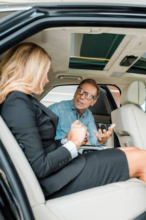 adult man and female car dealer sitting on back seat of luxury car and talking