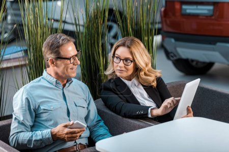 Photo for Happy adult man and female car dealer with phone and tablet sitting at showroom - Royalty Free Image