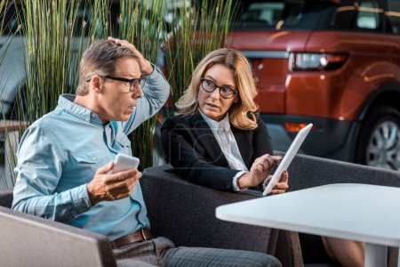shocked adult man and female car dealer with phone and tablet sitting at showroom