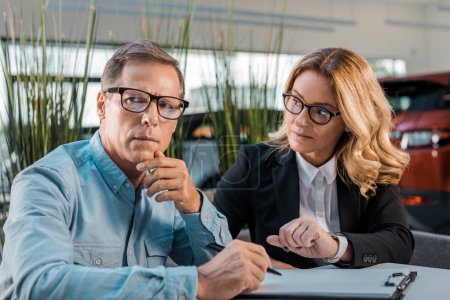 adult man and female car dealer sitting in showroom with contract
