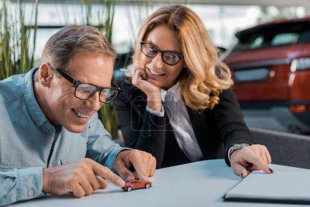 Photo pour Homme adulte heureux et concessionnaire féminin jouant avec voiture de jouet dans la salle d'exposition - image libre de droit