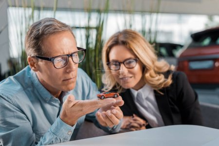 thoughtful adult customer and smiling female car dealer looking at toy car in showroom
