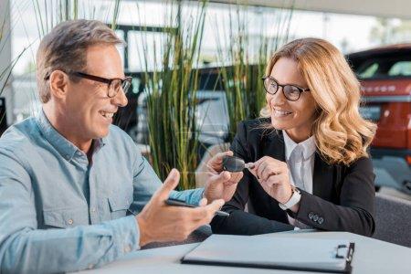 happy adult man and female car dealer passing car key in showroom