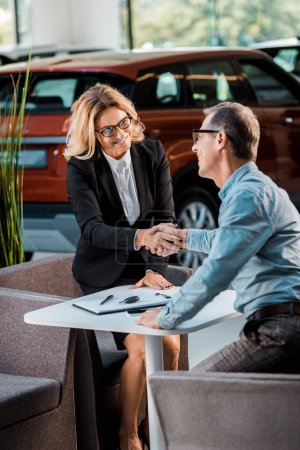 adult customer and female car dealer shaking hands in showroom