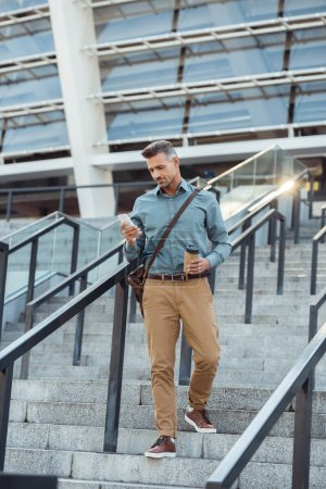 Photo for Handsome middle aged man holding paper cup and using smartphone on stairs - Royalty Free Image