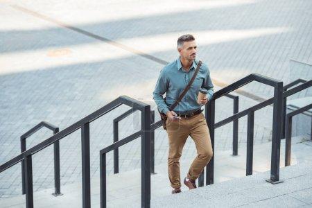 vista de ángulo alto del hombre sosteniendo la taza de papel y utilizando el teléfono inteligente en las escaleras