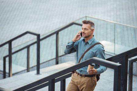 vista de ángulo alto del hombre de negocios de mediana edad hablando por teléfono inteligente y sosteniendo la taza de papel mientras está de pie en las escaleras