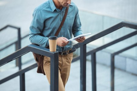 cropped shot of man using digital tablet while standing on stairs with coffee to go on railing