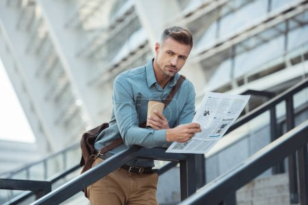 handsome middle aged man holding coffee to go and newspaper while standing on stairs
