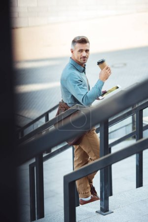 selective focus of handsome middle aged businessman drinking coffee from paper cup and using digital tablet on street