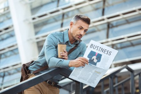 shocked middle aged man holding coffee to go and reading business newspaper