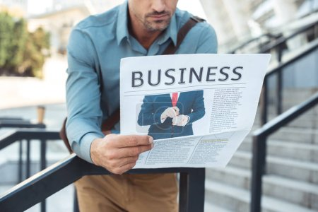 cropped shot of middle aged man leaning at railing and reading business newspaper