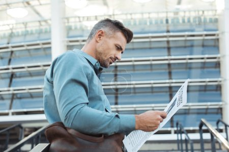 bajo ángulo vista de guapo de mediana edad hombre leyendo periódico de negocios en la calle